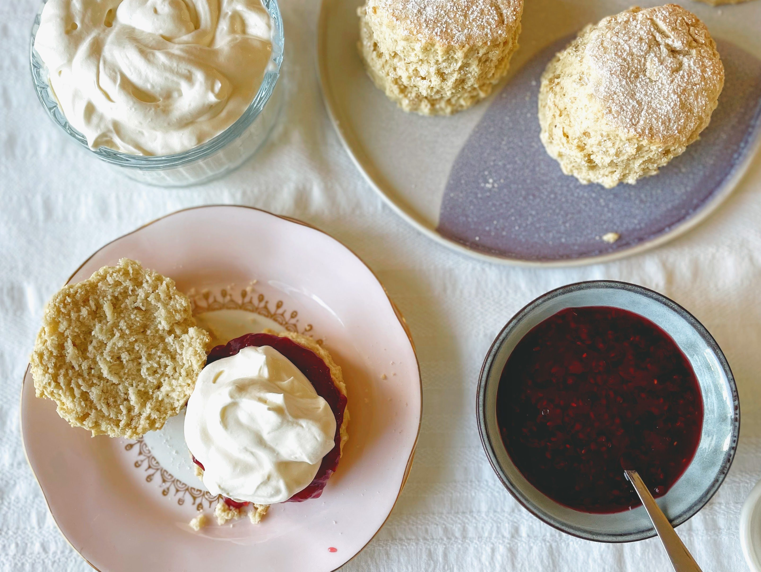 In the bottom left-hand corner of the picture there is a pale pink plate with a scone that has been split in two. One half reveals the soft, light crumb of the scone, and the other is smothered with crimson red raspberry jam and piled with whipped cream. There is a small bowl full of raspberry jam in the bottom right hand corner, and a dish of pillowy whipped cream in the top left. In the top right there is a blue patterned platter with the remaining scones, toweringly tall and with a little dusting of icing sugar on top.